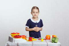 Girl on a toy kitchen Royalty Free Stock Images