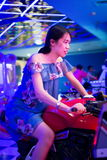 Girl on toy motorbike in an arcade Stock Photos