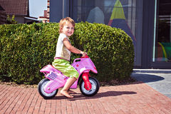 Girl on toy motorcycle Stock Photo