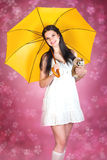 Girl with toy owl and yellow umbrella. Young woman holding a stuffed toy, pink floral background Stock Images