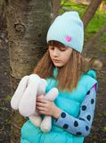Girl with a toy rabbit Stock Photography