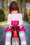 Girl on toy racing car. Girl in retro racing hat and goggles driving on toy car at speed with blurred background Stock Image