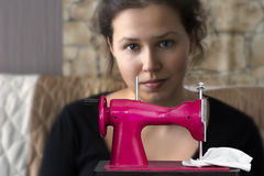 Girl with a toy sewing machine Royalty Free Stock Photo