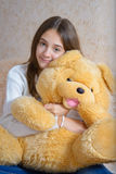 Girl and toy. Girl with toy sitting on the couch with a fur coverlet Royalty Free Stock Photography