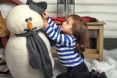 Girl with a toy snowman Royalty Free Stock Photography