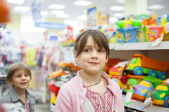 Girl in toy store choosing toys stock images