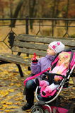 Girl with a toy stroller in autumn. Girl with a toy doll and a stroller in autumn outdoors royalty free stock photos