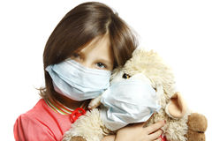 Girl with toy wearing a protective mask. Little girl with toy wearing a protective mask Royalty Free Stock Photography