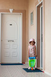Girl and toy wheelbarrow. Little beauty girl with toy plastic wheelbarrow at the threshold of the room stock photos