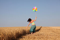 Girl with toy wind turbine at field. Village photos Royalty Free Stock Images