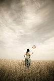 Girl with toy wind turbine at field. Village photos Stock Photos