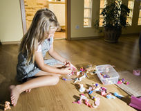 Girl with toys. A young girl sitting on the floor and playing with toys. Moody lighting Stock Photo