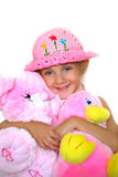 The girl with toys. The little girl smiles and embraces soft a toy - duck and a pig Royalty Free Stock Photo
