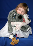 Girl with toys. Happy little girl with white dress embrace the toy grey dog Stock Photos