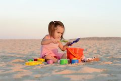 Girl with toys on the beach Stock Images