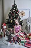 Girl with toys at the Christmas tree royalty free stock image