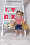 Girl with toys. Girl sitting on the stairs. The hand holds a teddy bear. On the stairs are books and letters Stock Image