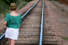 Girl on tracks. An adolescent girl walking to school on a set of railroad tracks with a book Royalty Free Stock Images