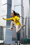 Girl in a tracksuit jumping. On the background of a big city Royalty Free Stock Image