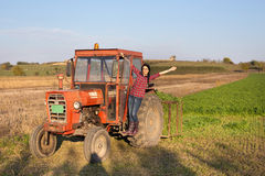 Girl in the tractor on farmland Stock Photos