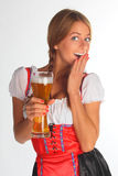The girl in a traditional Bavarian dress. With full glasses of beer in hands Stock Photos
