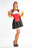 The girl in a traditional Bavarian dress. With full glasses of beer in hands Stock Images
