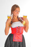 The girl in a traditional Bavarian dress. With full glasses of beer in hands Royalty Free Stock Photography