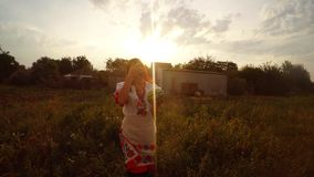 A girl in traditional folk dress of Ukraine finds and shows watermelon in the garden in the village in the evening. Collection, a girl in a traditional Ukrainian stock video footage