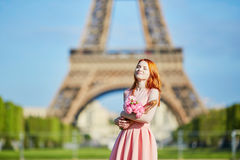 Girl with traditional French bread baguette and flowers in front of the Eiffel tower Royalty Free Stock Image