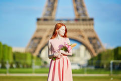 Girl with traditional French bread baguette and flowers in front of the Eiffel tower Royalty Free Stock Photo