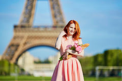 Girl with traditional French bread baguette and flowers in front of the Eiffel tower Stock Images