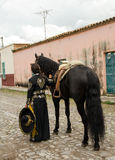 Girl in traditional Mexican outfit and black horse. Young woman in traditional Charro , Mexican, outfit with black Andalusian horse on cobblestone street royalty free stock photos