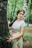 Girl in traditional Russian dress sarafan leaned against birch.  royalty free stock image