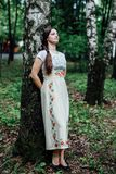 Girl in traditional Russian dress sarafan leaned against birch.  royalty free stock photo