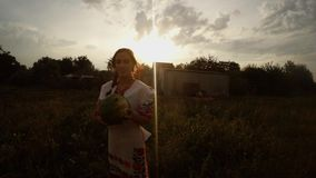 A girl in a traditional Urainian folk costume holds a watermelon in her hands. Collection, a girl in a traditional Ukrainian folk costume in the village stock video footage