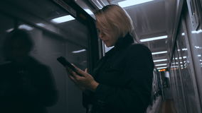 The girl in the train car uses a smartphone stock video