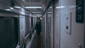 Girl on a train standing in an empty corridor and leaning on the window stock video