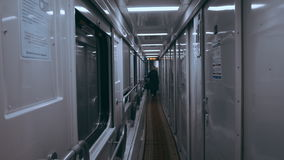 Girl on a train standing in an empty corridor and leaning on the window stock video footage