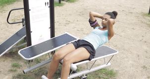 Girl training abs in park stock video