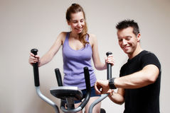 Girl on training apparatus. And instructor in sportclub Stock Photos