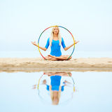Girl training on beach. Outdoor portrait of young beautiful blonde woman gymnast exercising with hoop on the beach Royalty Free Stock Photos