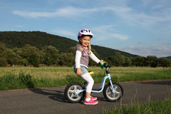 Girl on a training bike Royalty Free Stock Photo