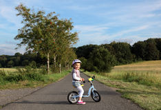 Girl on a training bike Stock Images