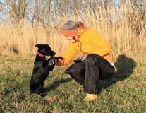 Girl training black dog Royalty Free Stock Image