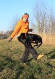 Girl training black dog Stock Image