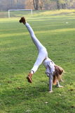 Girl training cartwheel. Exercising little kid - girl in grey clothes and brown shoes training cartwheel on green grass of football stadion Stock Images