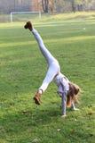 Girl training cartwheel Stock Images