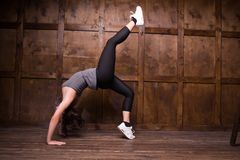 Fitness and exercice concept. Girl in training clothes isolated on wooden background. Doing exercises Stock Photos