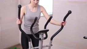Girl training on an elliptical trainer. Girl training on elliptical trainers at the gym stock video