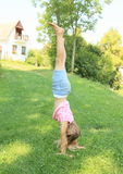 Girl training handstand. Exercising little kid - barefoot girl training handstand on green grass of village meadow Royalty Free Stock Image